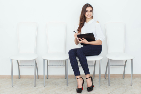 principal: The girl sits on a chair and fills up the documents