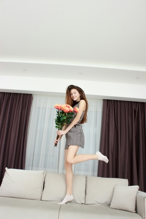 happy girl with big bouquet of pink roses, received as a gift Stock Photo