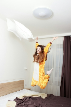 Funny girl in kigurumi pajamas jumping on the bed Stock Photo