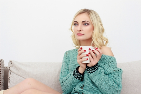 Portrait of beautiful young woman sitting on sofa at home with cup of tea in modern interior Stock Photo