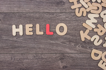 letterpress words: Word Hello made with wooden letters next to a pile of other letters over the wooden board surface composition