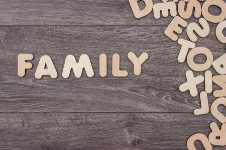letterpress words: Word Family made with wooden letters next to a pile of other letters over the wooden board surface composition