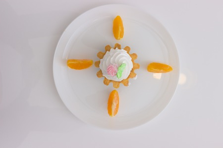 custard slice: cake basket with cream and orange slices on a plate isolated on white table. Top view.