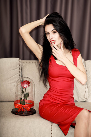 happy girl with rose, received as a gift in modern apartment