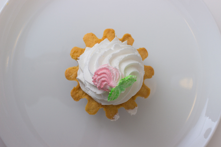 watered: cake basket with cream on a plate isolated on white table. Top view.