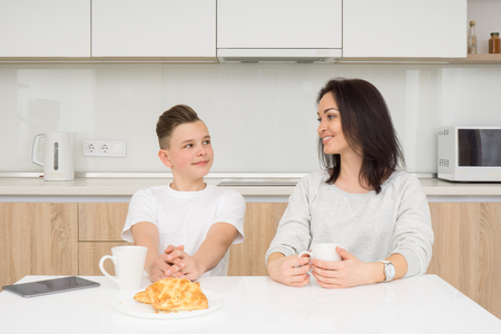 Happy family in the morning. Beautiful woman with her son having breakfast in kitchen. Looking on each other and smiling