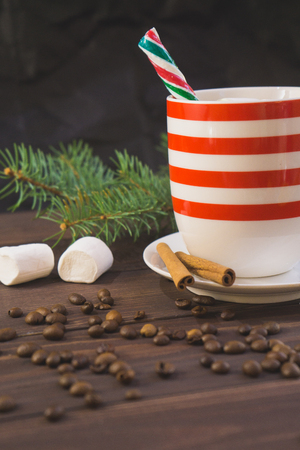 Cup of coffee and christmas snow fir branch on wooden table