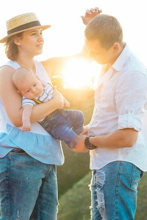 Happy family with little baby spending time together at sunset, on summer or autumn day, warm sunlight
