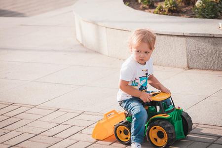Cute boy playing with toy tractor