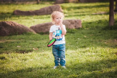 Cute little boy at summer day on green lawn