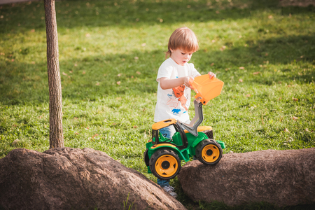 Cute boy playing with toy tractor at garden Stock Photo