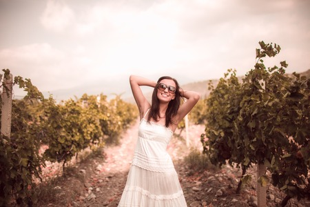 Smiling woman in white dress standing in vineyard Stock Photo