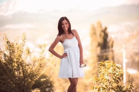 Smiling woman in white dress standing on beautiful crimea background Zdjęcie Seryjne