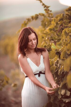 Smiling woman in white dress standing in vineyard Zdjęcie Seryjne