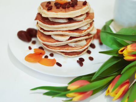 Stack of Pancakes on plate the Table with Tulips