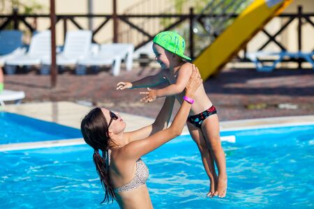 Mom holding baby in swimming pool. Mother and kid having fun on vacation at summer 版權商用圖片