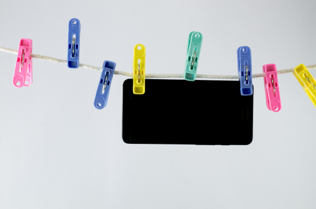 respond: Lots of clothespins Clamp telephone on a white background