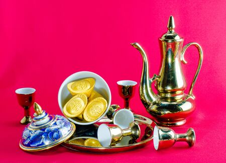 Gold ingot Gold jug Tea glass benjarong  on red background.