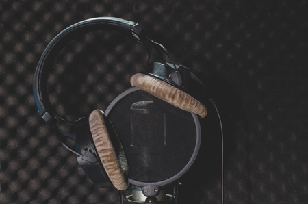 Headphone and microphone recording studio on a black background. Stock Photo