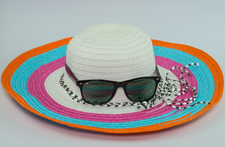sunhat: loppy beach hats sunglasses in various colors on white background