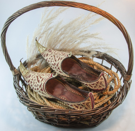 interleaved: Indian shoe king wicker brown basket isolated on white