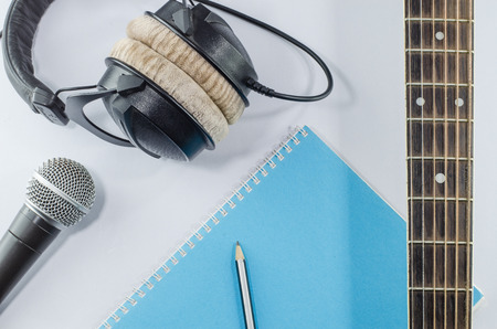 neck guitar notebook in top view with music concept whitebackground headphones