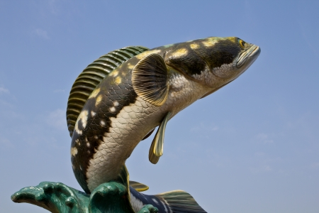 chevron snakehead: Striped snakehead fish sculpture in the blue sky Stock Photo