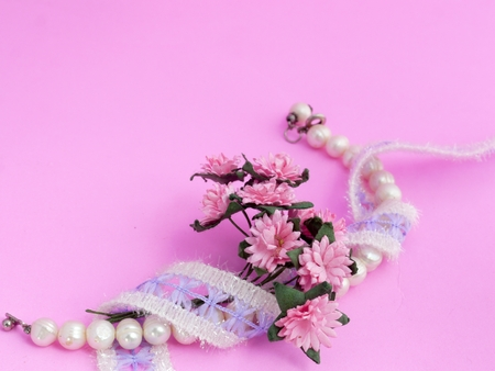 Pearl Bracelet, Lace and Daisy on Pink Background Stock Photo
