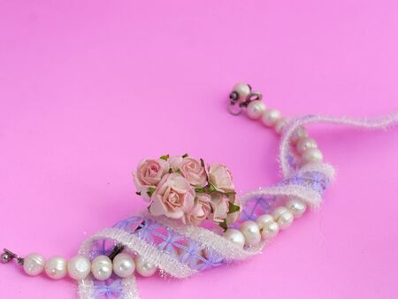 bolus: Pearl Bracelet, Lace and Roses on Pink Background