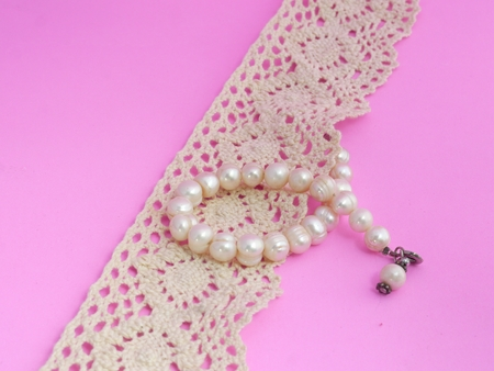 bolus: Pearl Bracelet and Lace on Pink Background