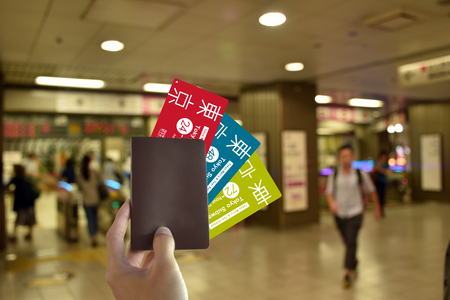 Hand with blank Passport and all subway  card of japan to travel in Tokyo on blurred subway background