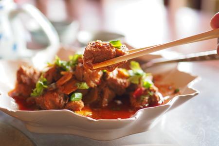 Spicy stir-fried pork on chopsticks Stock Photo
