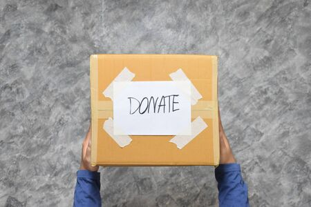 Man holding a Donate Box for Giving on Polished Cement background.Top View.