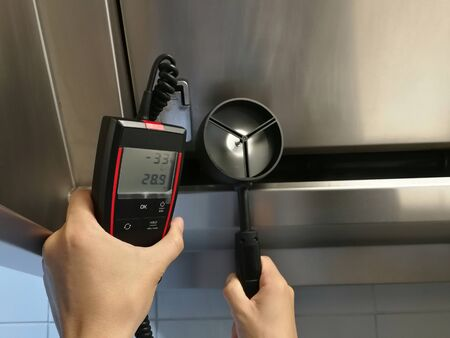 The inspectors are using aneamometer to measure the air velocity of the hood in the kitchen. Foto de archivo