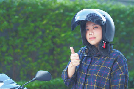 A Young Woman fastening or Wearing her motorbike helmet with blur Fukien tea tree Carmona retusa green background - Zero accident concept