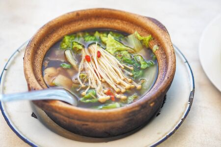 Bak kut teh or Hokkiens topping with golden needle mushroom or Enokitake in Earthenware pot in broth popularly served in Malaysia ,Singapore and and Southern Thailand.