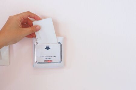 Soft Focus on Hand insert key card for on power electric equipment in the hotel room, Hotel Lock Energy Control System