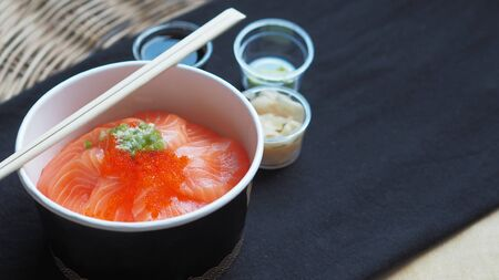 Side view of Salmon with Japanese rice or Salmon Ikura Don in paper dish from delivery restaurant on black Table cloths