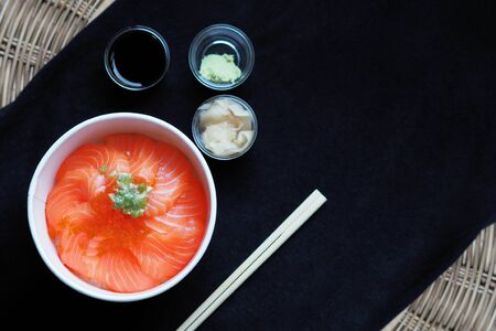 Top view and focus to Salmon with Japanese rice or Salmon Ikura Don in paper dish from delivery restaurant on black Table cloths Archivio Fotografico