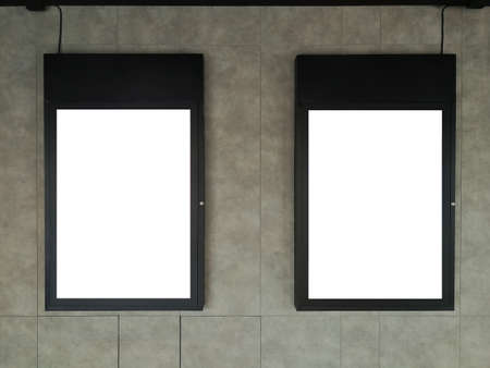 Soft focus on Two Black frame advertising signs with white background on bare cement or concrete wall