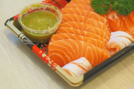 Soft Focus to Sashimi salmon topping with Parsley and Thai Seafood Dipping Sauce on Japanese Plastic Plates Archivio Fotografico