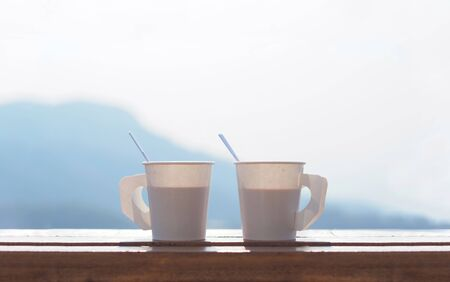 Coffee in a paper cup on a wooden table in the morning with Blurred Mountain background and copy space on top of image.