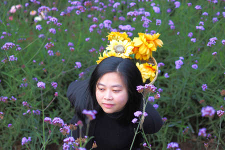 Top view of Asian Young woman  carrying a basket and has sunflower in verbena flower gardens at Mon Jam, Thailand. Archivio Fotografico