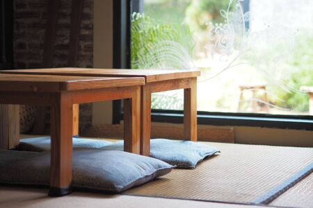 Japanese-style room decoration with wooden tables and sitting cushions floor, Green garden background.