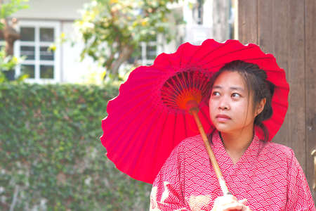 Soft focus on Traditional Japanese Yukata young girl with red umbrella in garden, Asian girl in Yukata with umbrella, Japanese tradition concept Archivio Fotografico