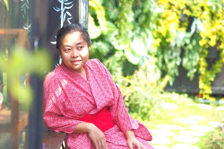 Soft focus on Asian woman wearing kimono or yukata in Japanese style Garden.