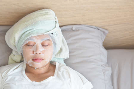 Soft focus on Asian young woman with a sheet mask on her face. - Wellness face care and Spa Concept.