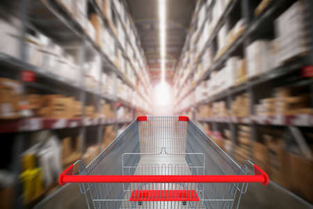 First person view or back view of Supermarket aisle with empty red shopping cart with blurred supermarket background. Standard-Bild