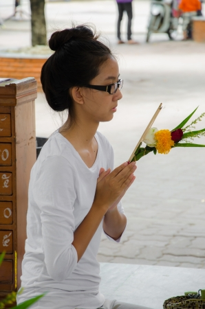 Thai girl pay respect to god of buddha with strong faith photo