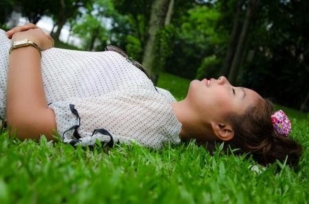 Thai girl sleep on grassland,relax time Stock Photo - 14332915